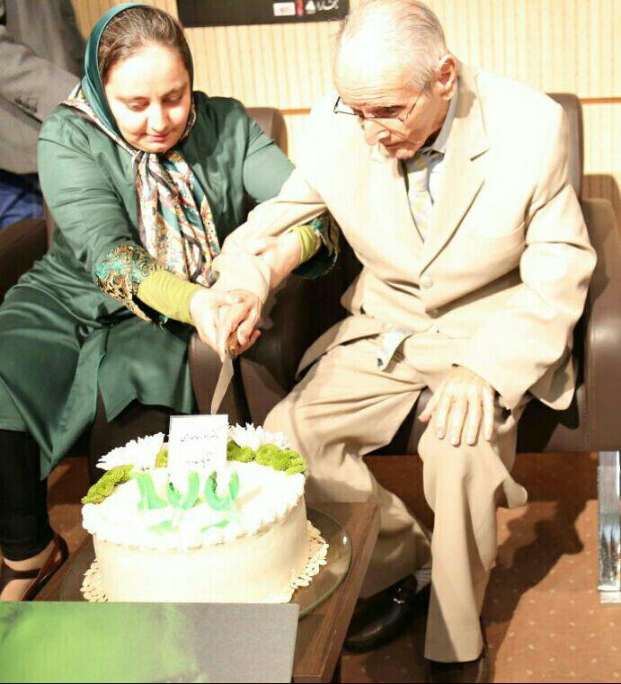 دکتر انور خامه ای به همراه دخترش، ملیحه، کیک تولد صد سالگی اش را می برد
