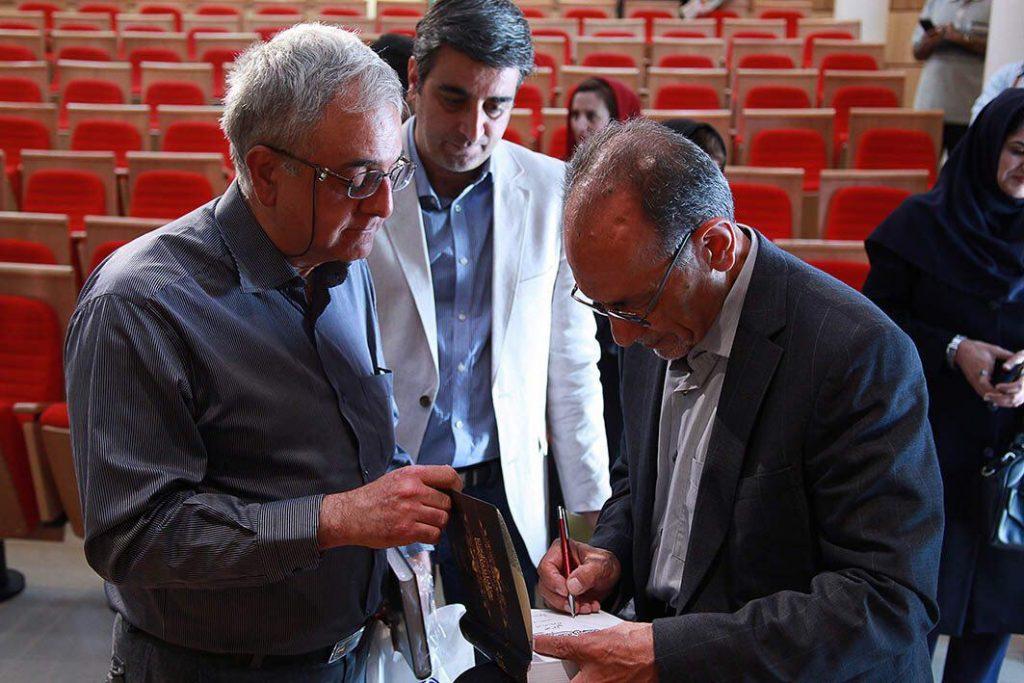 دکتر سرور مولایی کتابی را برای دکتر قباد امضا می کند