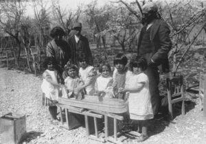 جبار باغچهبان و بلقیس نمازی، مربی کودکستان درکنار کودکان کودکستان در حال رختشویی ـ شیراز، سال 1307